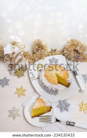 Festive pumpkin cake with coconut on table and Christmas decoration. Background bokeh. From series of Winter pastries