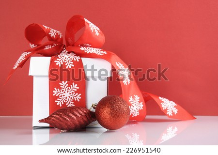 Festive red and white theme Christmas gift box on reflective white table against a red background.