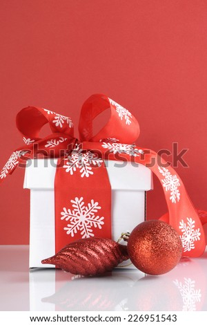 Festive red and white theme Christmas gift box on reflective white table against a red background. Vertical with copy space.