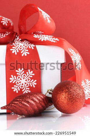Festive red and white theme Christmas gift box on reflective white table against a red background. Close up.