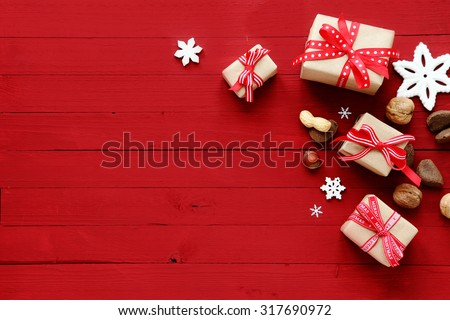 Festive red Christmas card background with copyspace and a holiday border of decorative Xmas gifts, snowflake ornaments and assorted fresh whole nuts #317690972