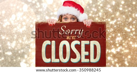 Festive redhead smiling at camera holding poster against vintage closed sign
