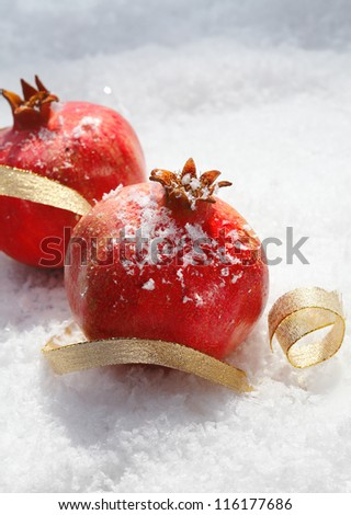 Festive ripe red pomegranates with decorative gold ribbon nestling in fresh winter snow with copyspace for your Christmas greeting