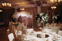 Festive served table with a bouquet of white and pink roses. Banquet table covered with white tablecloths with white plates, silver cutlery, white napkins with pink ribbon