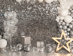 Festive silver background mosaic with light spots with silver glittering decorations. Disco balls on silver wall. Christmas, Wedding, Birthday, New Year concept. Copy space..