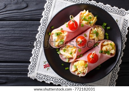 Festive snack: roll ham stuffed with scrambled eggs and tomatoes close-up on a plate. horizontal top view from above