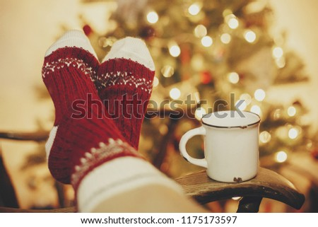 festive socks and mug with hot drink on old wooden chair on background of golden beautiful christmas tree with lights in festive room. cozy winter holidays. warm atmospheric moment