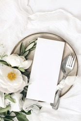 Festive summer wedding scene. Marble table setting with cutlery, olive branches, white peony flowers, stoneware plate and silk ribbon. Blank restaurant menu card mockup. Flat lay, top view, vertical.