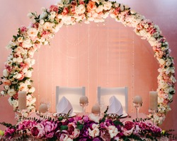 Festive table, arch, stands decorated with composition of violet, purple, pink flowers and greenery, candles in the banquet hall. Table newlyweds in the banquet area on wedding party.