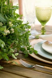 Festive table decor in openair next to the pond. Green color with wooden cutlery. Different natural white flowers. Wooden table and chairs. Wine glasses. Luxury wedding, party, birthday.