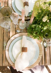 Festive table decor in openair next to the pond. Green color with wooden cutlery. Different natural white flowers. Wooden table blue plates. Luxury wedding, party, birthday. View from above. Top view.