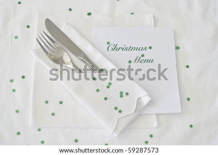 Festive table place setting with shiny green stars and Christmas  menu