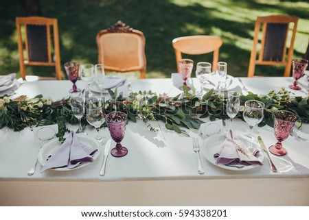 Festive table served dishes and decorated with branches of greenery, stands on green grass in the area of wedding party