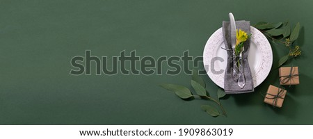 Festive table setting concept with vintage plate and cutlery set, aromatic eucalyptus twigs and gift boxes on deep green background. Long banner format. Photo stock ©