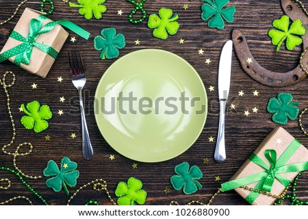 Festive table setting for St.Patrick's day with cutlery and lucky symbols on wooden table. Copy spase, top view.