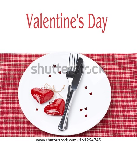 Festive table setting for Valentine's Day with fork, knife and hearts, isolated on white