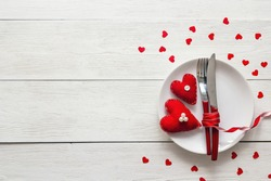 Festive table setting for Valentine's Day with fork, knife and hearts on a white wooden table. Space for text. Top view.