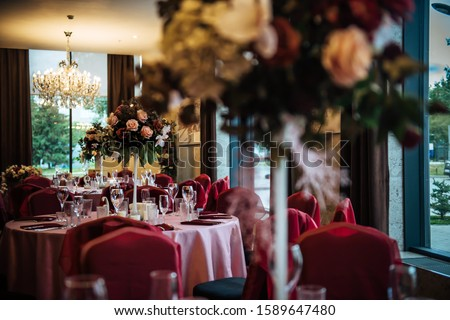 Festive table setting in the restaurant, preparation for the celebration, anniversary. Wedding Banquet, tables decorated with flowers.