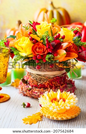 Festive table setting with basket of autumn flowers,candle and pumpkin #207562684
