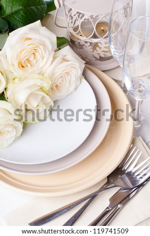 Festive table setting with beige roses, wine glasses, candles, napkins and cutlery