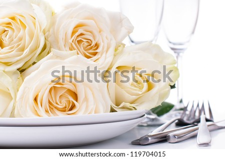 Festive table setting with beige roses, wine glasses, candles, napkins and cutlery, isolated - stock photo