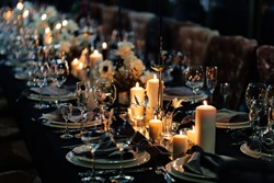 festive table setting with candles for wedding party in the dark