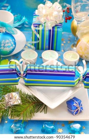 festive table setting with christmas cracker on square shape plates