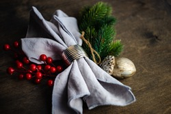 Festive table setting with napkin in ring decorated with red berries and christmas tree branches on wooden table
