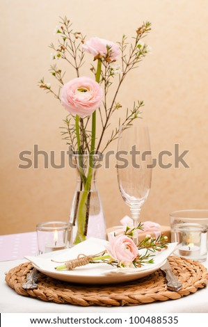 Festive table setting with pink flowers and candles