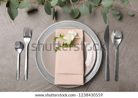 Festive table setting with plates, cutlery and napkin on grey background, flat lay