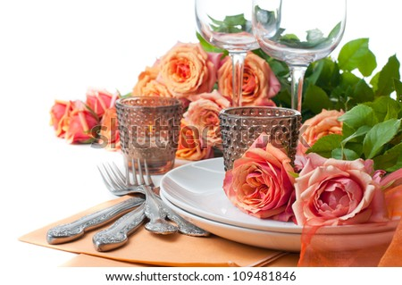 Festive table setting with roses and candles in shades of orange on a white background