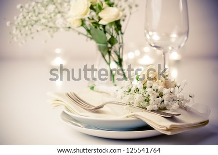 Festive table setting with roses in bright colors and vintage crockery on a beige background