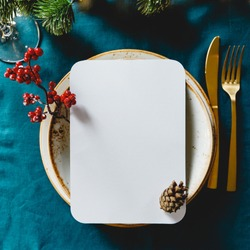 Festive table setting with winter decor and mockup. The concept of Thanksgiving or Christmas family dinner.