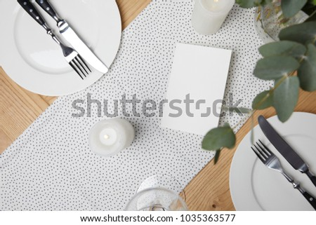Festive table with cutlery on plates on table with candles #1035363577