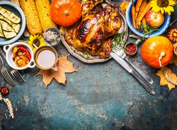 Festive  Thanksgiving Day food background with roasted whole turkey or chicken and sauce, harvest vegetables: corn, pumpkin,carrots with cutlery on dark rustic kitchen table, top view, border
