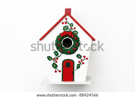 Festive Winter Birdhouse with wreath and Holly isolated on white background