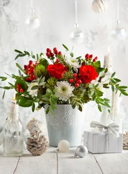 Festive winter flower arrangement with red roses, white chrysanthemum and berries in vase on table decorated for holiday. Christmas or New Year concept.