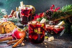 Festive winter fruit punch or sangria drink. Christmas mulled red wine. Ponche de frutas Navideño cocktail, Mexian Christmas hot  beverage with sugar cane and fruit, hot sweet liquor wine drink