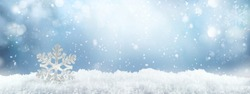 Festive winter snow background with snowdrifts, silver decorative snowflake with beautiful light and snow flakes on blue sky, banner format, copy space.
