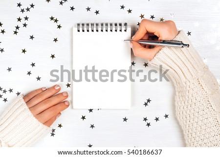 Festivedecorations and notebook with wish list on white rustic table, flat lay style. Planning concept.
