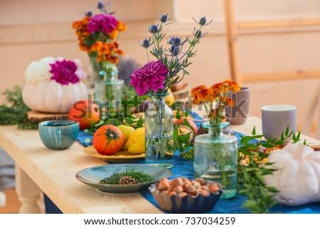 festively served autumn table, autumn food and paraphernalia, pumpkins, flowers, tea