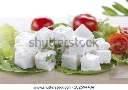 feta cheese cut in cubes, vegetables, herbs and olive oil-the ingredients for a greek salad