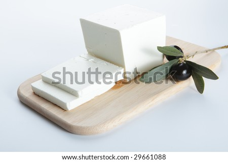Feta cheese with olive on a wooden cutting board