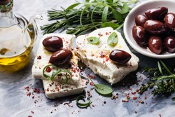 Feta cheese with olives and green herbs on gray marble background