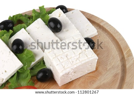 feta cheese with olives on wooden plate
