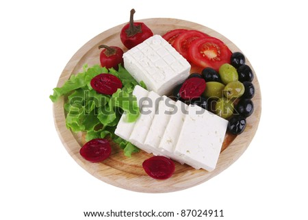 feta cheese with olives on wooden plate - stock photo