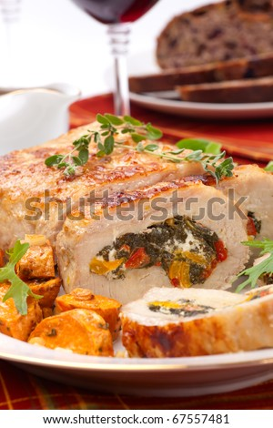 Feta-, spinach-, and bell pepper - stuffed pork tenderloin roulade garnished with sweet potato and green salad.