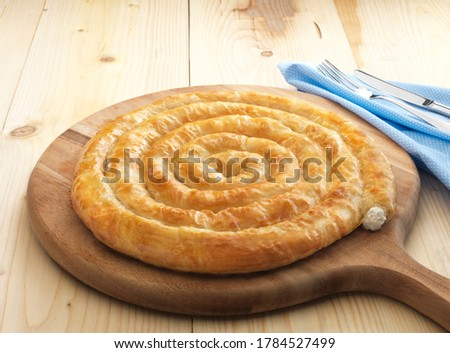 Feta Twist Pie on the wooden. A traditional Turkish tepsi boregi, rulo borek. Greek cheese pie with feta, goat, spinach or meat. With cloth napkin, fork and knife on wooden floor. Stock fotó ©