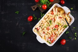 Fetapasta. Trending viral Feta bake pasta recipe made of cherry tomatoes, feta cheese, garlic and herbs in a casserole dish. Top view, above, copy space.