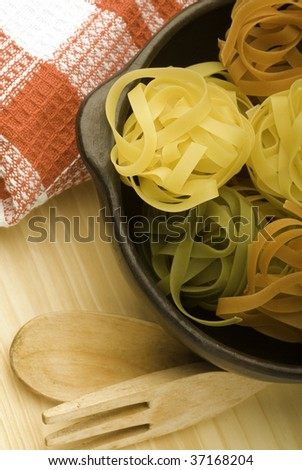 fettuccine nests in clay pots and wooden cutlery